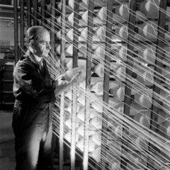 A mill worker beams threads of asbestos material at Turner Asbestos.