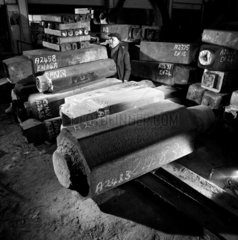 A man marks steel ingots on shop floor for Spear and Jackson tool production.