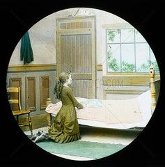 A girl kneeling in prayer at her bedside  magic lantern slide  c 1890.