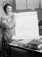 Woman holding a freshly laundered sheet  1950.