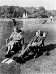 Elderly couple relaxing by a lake  1956.