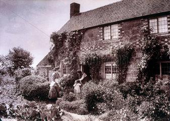 Two women and children in cottage garden  c
