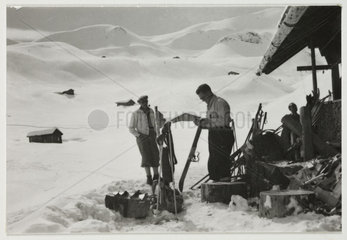 Skiers outside a chalet  c 1930.