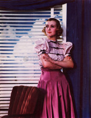 Woman standing by a window with blinds  c 1940s.
