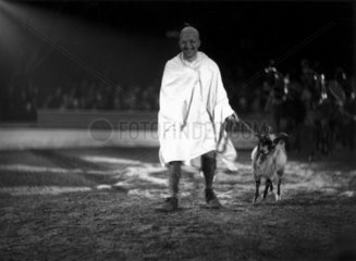 'Mahatma Gandhi' leading a goat around a circus ring  c 1930s.