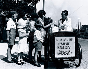 Children buying ice cream from a street vendor  c 1920s.