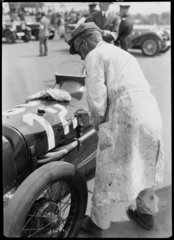 Sign-writer painting the number on an Austin racing car  Berlin  1933.