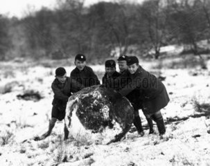 Schoolboys rolling a giant snowball  c 1930.