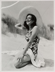 Woman on a beach in sunhat and swimsuit  c 1935.