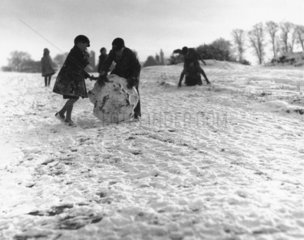 Schoolboys rolling a giant snowball  c 1930s.
