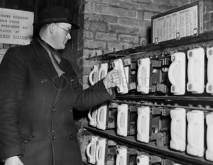 Man removing a fuse at electricity substation  12 February 1947.