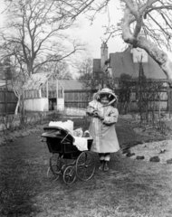 Girl with a pram full of dolls  c 1910s.