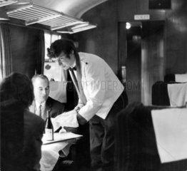 Brian Vaughan  steward  serving wine to passengers  15 October 1971.
