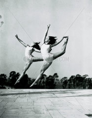 Two women gymnasts in mid-air  c 1930s.