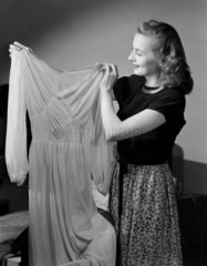 Woman admiring an evening dress  1952.