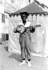 Black and white minstrel playing a banjo  c