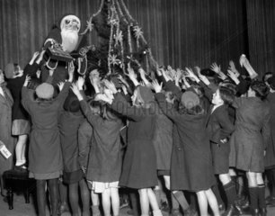 Father Christmas distributes toys to poor children  7 December 1934.