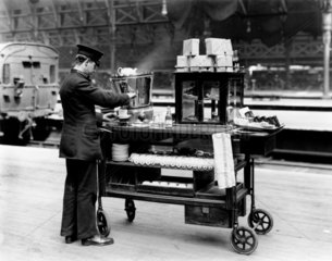 Attendant filliing teacup with boiling water from urn on trolley  19 April 1921.