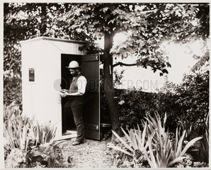 Man inspecting a photographic plate outside his darkroom  c 1900s.