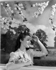 Woman beneath a flowering tree  c 1950.