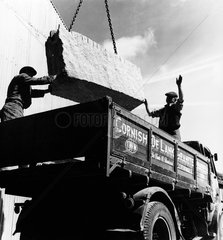 Quarry workers in Cornwall load granite block on to lorry  1961.
