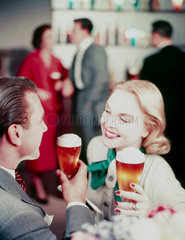 Couple drinking beer  c 1950s.