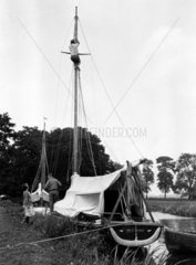 Man climbing the mast of a yacht which is m