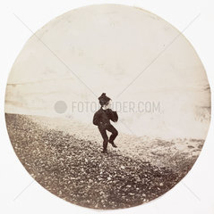 Boy running along the shoreline  c 1890.