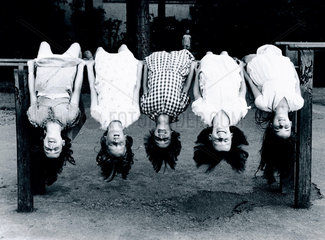 Five young girls hanging upside-down from a railing  c 1930s.