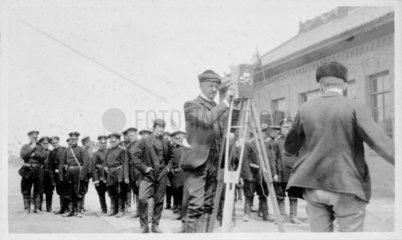 Cameraman cranking a camera  c 1904.
