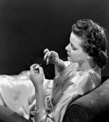 Woman sitting in a chair painting her nails  c 1940s.