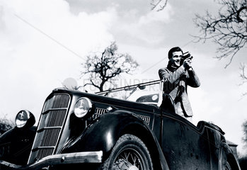 Man standing in a Ford motor car  filming with a cine camera  c 1930s.