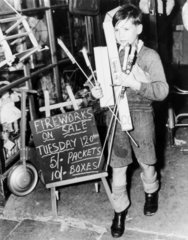 Boy carrying fireworks  18 October 1949.