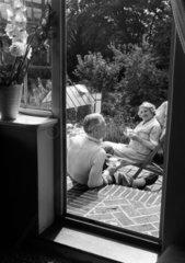 Elderly couple taking tea in the garden  1953