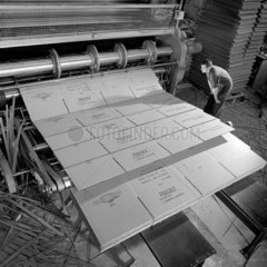 A worker inspects finished rolls of card board on a Greenwood machine  1964.