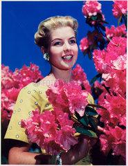 Woman standing near flowering shrubs  c 1940s.