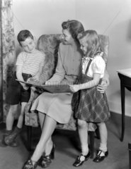 Woman reading a story to two children  1949.