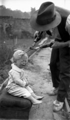Man cutting crying child's hair with garden shears  c 1920s.