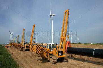 Schulzendorf  Deutschland  Seitenbaumraupen heben ein Teilstueck der OPAL-Gasleitung an