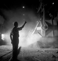 Steelworker silhouetted against ladle of molten metal   United Steel  1947.