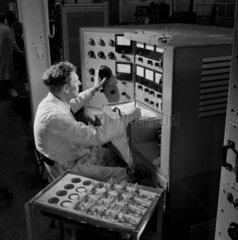 An engineer inspects valves  Mullard Ltd  1955.
