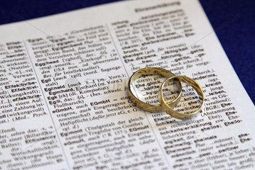 Berlin  Deutschland  zwei goldene Ringe liegen auf dem Wort Eheglueck
