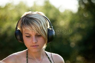 Freiburg  Deutschland  junge blonde Frau hoert Musik mit Kopfhoerern
