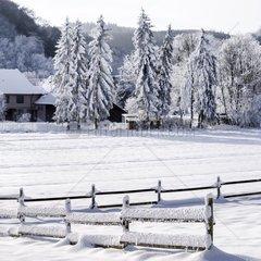 Verschneiter Zaun in Winterlandschaft.