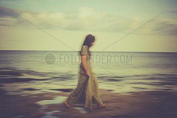 Frau schlendert am Meeresufer
