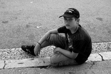 Junge sitzt auf der Strasse am Gehweg