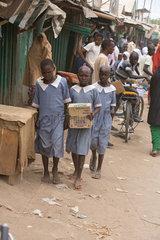Kakuma  Kenia - Strassenszene. Schuelerinnen in Schuluniformen im belebten Strassenbild.