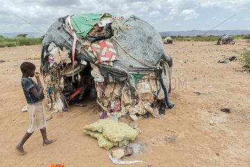 Kakuma  Kenia - Am Rande des Fluechtlingslagers Kakuma. Ein Maedchen steht vor einer  von alten Plastikplanen  Decken  Kartons und Muell bedeckten Huette.