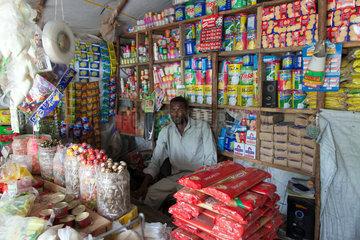 Kakuma  Kenia - Ein Verkaeufer sitzt in einem kleinen Lebensmittelladen in Kakuma Stadt.