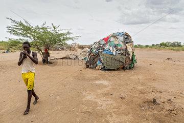 Kakuma  Kenia - Am Rande des Fluechtlingslagers Kakuma. Ein junger Mann telefoniert mit seinem Handy.